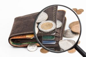 Wallet with some change and a magnifying glass