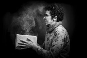 Man with a dusty book thinking about the benefits of climate controlled storage.
