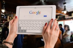 A woman using a tablet and Google Search engine.