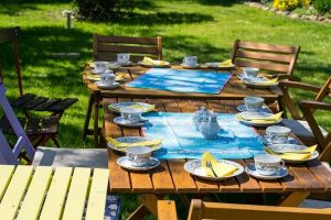 Chairs and tables with tea cups and plates in a garden.