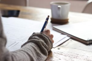 A student studying hard and writing at a desk, activities that are an essential part of the tips for Hong Kong students applying for NYU