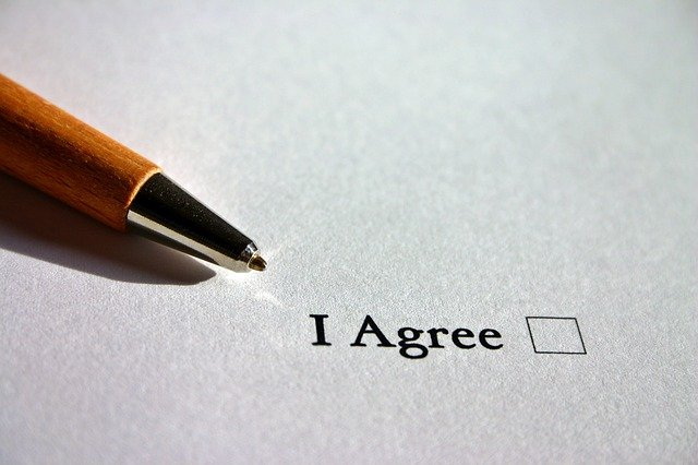 """""""I agree"""" written on a piece of paper, with a pen next to it."""