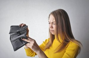 A girl is holding a black wallet.
