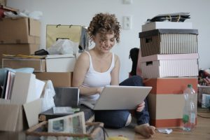 A girl is sitting on the floor surrounded by some boxes, and she is typing something on her laptop.