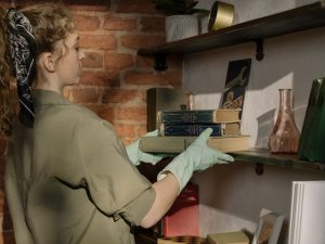 There is a girl tidying things on a shelve as cleaning is one of the chores that will be much easier if you declutter your home regularly.
