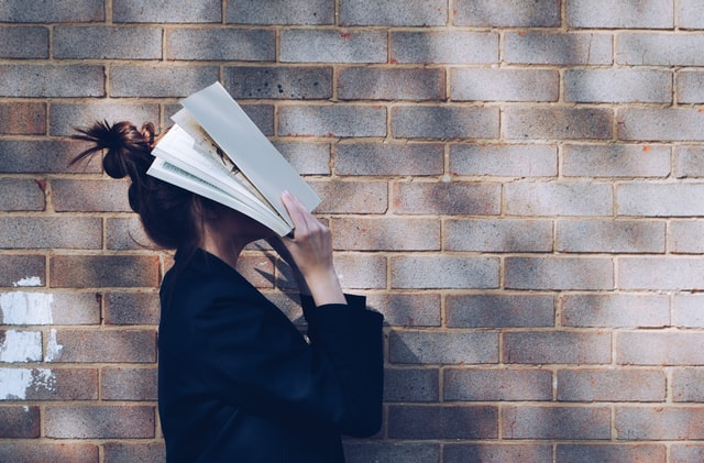 A girl holding her head inside a book