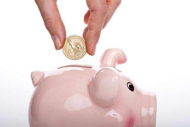 A person holding a coin over a pink piggy bank