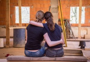 Two girls hugging from their back while sitting on a bench inside a house.