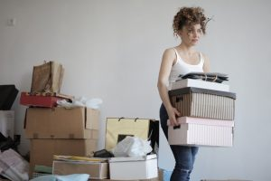 An anxious-looking woman carrying a stack of cardboard boxes