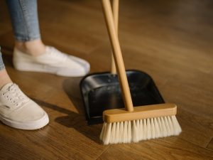 A female person brooming the floor depicting what one shouldn't forget to do when the last minute move takes place