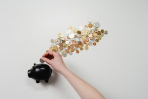 A person is putting a coin in a piggy bank.