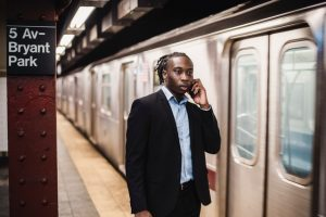 A man at a metro station is talking on the phone. Learning how to use the subway is one of the best advices in the Philadelphian's guide to surviving New York City.