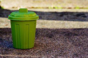 Green bin on the ground.