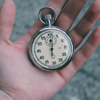 A person holding a stopwatch, with a plan on how to speed up your Manhattan move.