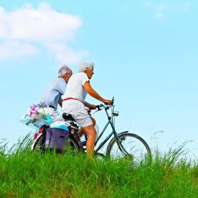 An elderly couple cycling and discussing the best Queens neighborhoods for retirees.