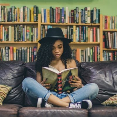A girl holding a book and reading about home insurance quotes.