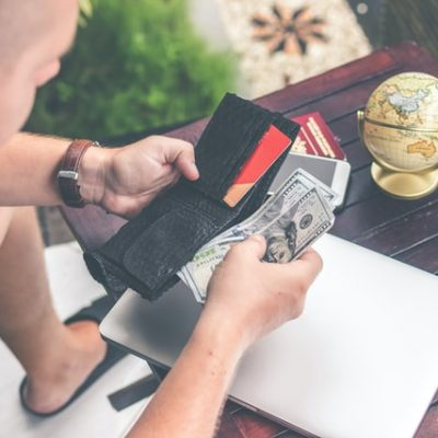 A man holding a wallet and counting money