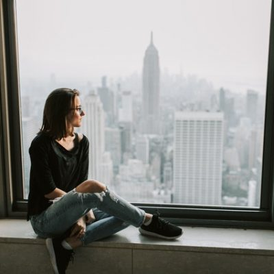 A girl is sitting by the window and thinking about surviving New York City